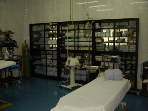 A view of the operating room with the large supply shelves that form the wall between the OR and the sterilization room.  There are glass doors on both sides to allow access to the shelves from either room.  This allows much better organization of the supplies and makes taking inventory a easier process.