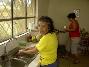 Esther is washing something while Damarys is working the stove.