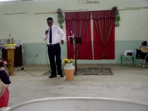 The pastor as he is delivering his sermon to us.